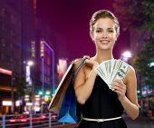 sale, money, people and holidays concept - smiling woman in evening dress with shopping bags and dollars over city background