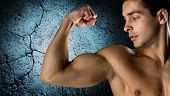 sport, bodybuilding, strength and people concept - close up of young man flexing and showing biceps over concrete wall background
