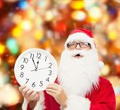 christmas, holidays and people concept - man in costume of santa claus with clock showing twelve over red lights background
