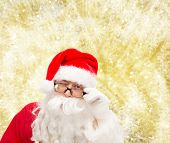 christmas, holidays and people concept - close up of santa claus in glasses winking over yellow lights background