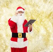christmas, holidays, technology and people concept - man in costume of santa claus with tablet pc computer over yellow lights background
