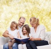 family, childhood, holidays and people - smiling mother, father and little girls reading book over yellow lights background