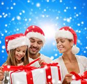 family, christmas, generation, holidays and people concept - happy family in santa helper hats with gift boxes sitting over blue snowy background