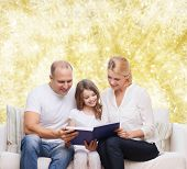 family, childhood, holidays and people - smiling mother, father and little girl reading book over yellow lights background