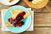 Delicious pancakes with berry jam  and bananas on plates on wooden background