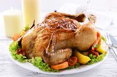 Delicious baked chicken on plate on table on light background