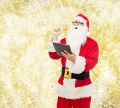 christmas, holidays, technology and people concept - man in costume of santa claus with tablet pc computer pointing finger up over yellow lights background