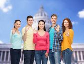 friendship, tourism, travel and people concept - group of smiling teenagers showing ok sign over white house background