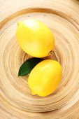 Ripe lemons on wooden plate close-up