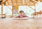 Blue eyes blonde boy lying on the wooden floor