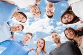 picture of huddle  - Directly below portrait of happy multiethnic friends forming huddle against sky - JPG