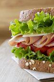 Ham sandwich on a wooden cutting board