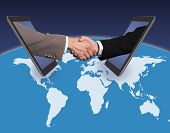 Business Handshake Emerging From Digital Tablets On World Map