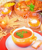Cream of pumpkin soup on festive table near baked turkey and different tasty dishes, delicious veggie soup, Thanksgiving day concept