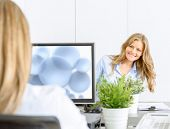 Two female coworkers at the office, sitting face to face in an open space