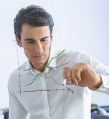 Businessman drawing a chart in a glass wall
