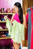 Asian young woman choosing dress in fashion store