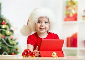 kid girl in christmas hat with tablet pc