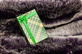 Green Gift Box On Wool Texture.