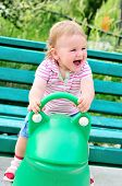 stock photo of baby frog  - Small funny girl girl on spring frog swing - JPG