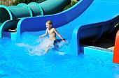stock photo of little boys only  - Cute little boy sliding down a water slide to pool - JPG