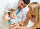 Pediatrician doctor examining child. Mother holding baby.