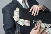 Businessman With A Briefcase Full Of Money In The Hands Of