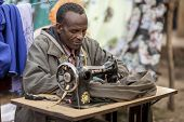 OROMIA, ETHIOPIA: NOVEMBER 5, 2014- An unidentified tailor sews clothing in a market in Oromia, Ethiopia