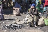 OROMIA, ETHIOPIA-NOVEMBER 5, 2014: An unidentified woman sells charcoal at an open air market in Ethiopia.