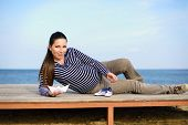 stock photo of booty  - pregnant woman on the beach with paper boat and striped booties - JPG