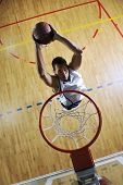 pic of indoor games  - young healthy man play basketball game indoor in gym