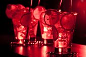 stock photo of collins  - Four Tom Collins cocktails shot on a bar counter in dim light - JPG