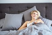 pic of beside  - A woman resting in bed with hands beside her head on the pillow - JPG