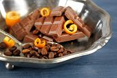 pic of orange peel  - Chocolate with orange peels and coffee beans in metal tray on wooden table - JPG
