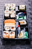 stock photo of lunch box  - a sushi box or bento box with assorted sushi pieces over a dark black lunch mat - JPG