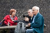 image of grandparent child  - Seniors with child on family hiking trip relaxing outdoors - JPG