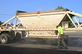 stock photo of dump_truck  - A large belly dump truck delivers fresh asphalt for a paving project of a new road and intersection project - JPG