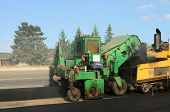 pic of paving  - Asphalt paving machine laying down a fresh layer of paving on a new road interchange project - JPG