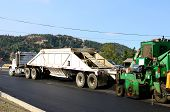 picture of dump_truck  - A large belly dump truck delivers fresh asphalt for a paving project of a new road and intersection project - JPG