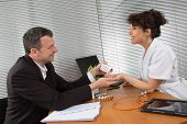 foto of prophylactic  - Businessman with Female Doctor at her office - JPG