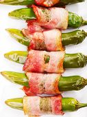 foto of jalapeno  - Grilled jalapenos wrapped in bacon isolated on white - JPG