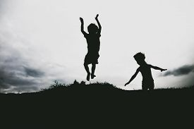 picture of jumping  - Silhouettes of kids jumping from a sand cliff at the beach - JPG