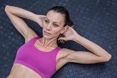 stock photo of crunch  - Upward view of a muscular woman doing abdominal crunch - JPG