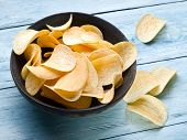 image of potato chips  - Potato chips on a blue wooden background - JPG