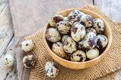 picture of quail  - Quail eggs in wooden bowl on a wooden table background - JPG