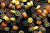 picture of wagon wheel  - Dry coloured wagon wheel pasta on black textured wood from above - JPG
