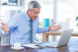 foto of confusing  - Confused businessman looking at laptop computer in office - JPG