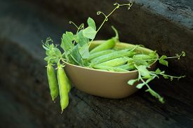 picture of pea  - brown ceramic bowl with open green peas on old wood - JPG