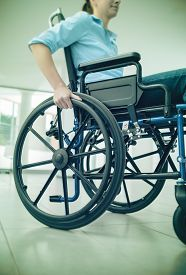 stock photo of handicapped  - Young woman in wheelchair hand pushing on wheel close up disability and handicap concept - JPG