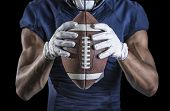 Постер, плакат: Close up view of an American Football player holding a football Selective focus on the laces of the